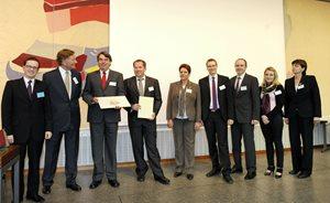 Die Gewinner von AUDI, Personen vor einer Wand. 2 halten die Urkunden